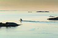 Båt i skymning i ytterskärgården vid spegelblankt Kallskär i Stockholms skärgård/ Stockholm archipelago Sweden