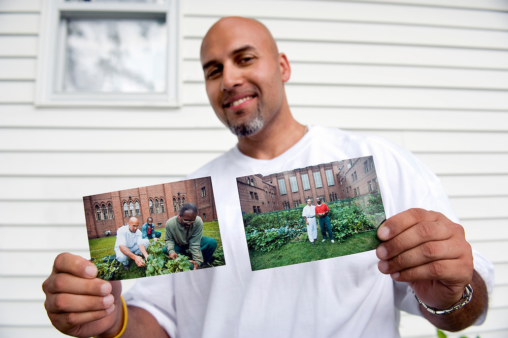 """Carlos Rosario at his home near Poughkeepsie, New York. He is holding tow photographs showing him and fellow inmates working at 'his' garden at the Woodbourne Correctional Facility. He was released from prison in May 2010. ..Story: The Bard Prison Initiative.Former inmate Carlos Rosario, 35-year-old husband and father of four, was released from Woodbourne Correctional Facility after serving more than 12 years for armed robbery. Rosado is one of the students participating in the Bard Prison Initiative, a privately-funded program that offers inmates at five New York State prisons the opportunity to work toward a college degree from Bard College. The program, which is the brainchild of alumnus Max Kenner, is competitive, accepting only 15 new students at each facility every other year. .Carlos Rosario received the Bachelor of Arts degree in social studies from the prestigious College Saturday, just a few days after his release. He had been working on it for the last six years. His senior thesis was titled """"The Diet of Punishment: Prison Food and Penal Practice in the Post-Rehabilitative Era,"""".Rosado is credited with developing a garden in one of the few green spaces inside the otherwise cement-heavy prison. In the two years since the garden's foundation, it has provided some of the only access the prison's 800 inmates have to fresh vegetables and fruit...Rosario now works for a recycling company in Poughkeepsie, N.Y...Photo © Stefan Falke"""