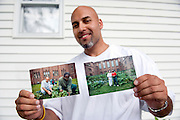 "Carlos Rosario at his home near Poughkeepsie, New York. He is holding tow photographs showing him and fellow inmates working at 'his' garden at the Woodbourne Correctional Facility. He was released from prison in May 2010. ..Story: The Bard Prison Initiative.Former inmate Carlos Rosario, 35-year-old husband and father of four, was released from Woodbourne Correctional Facility after serving more than 12 years for armed robbery. Rosado is one of the students participating in the Bard Prison Initiative, a privately-funded program that offers inmates at five New York State prisons the opportunity to work toward a college degree from Bard College. The program, which is the brainchild of alumnus Max Kenner, is competitive, accepting only 15 new students at each facility every other year. .Carlos Rosario received the Bachelor of Arts degree in social studies from the prestigious College Saturday, just a few days after his release. He had been working on it for the last six years. His senior thesis was titled ""The Diet of Punishment: Prison Food and Penal Practice in the Post-Rehabilitative Era,"".Rosado is credited with developing a garden in one of the few green spaces inside the otherwise cement-heavy prison. In the two years since the garden's foundation, it has provided some of the only access the prison's 800 inmates have to fresh vegetables and fruit...Rosario now works for a recycling company in Poughkeepsie, N.Y...Photo © Stefan Falke"