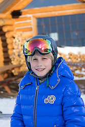 boy in a winter coat and goggles by a ski lodge