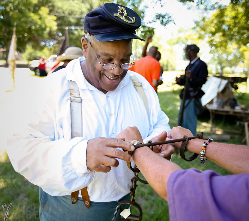 JAMES ISLAND, SC - JULY 18: Reenactor Mel Turner, with the 54th Regiment Massachusetts Volunteer Infantry, demonstrates how shackles work after ceremonies at Seashore Farmers' Lodge on James Island. (Photo by Paul Zoeller/For the Washington Post)