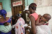 A woman waits with her child to pick up a prescription at the Koumassi General hospital in Abidjan, Cote d'Ivoire on Friday July 19, 2013.