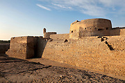 Spur Tower, which protected the keep or Captain's Tower, and on the left, Genoan style bastion, built 1561 AD, at Qal'at al-Bahrain, or Bahrain Fort or Portuguese Fort, built 6th century AD, once the capital of the Dilmun Civilisation, near Manama in Bahrain. The site consists of a tell or artificial mound 12m high containing 7 layers of archaeological remains dating from 2300 BC to the 18th century, topped with a medieval fortress. There is evidence of Kassites, Greeks, Portuguese and Persians, with burial sites, fortifications and residential areas. Qal'at al-Bahrain is listed as a UNESCO World Heritage Site. Picture by Manuel Cohen