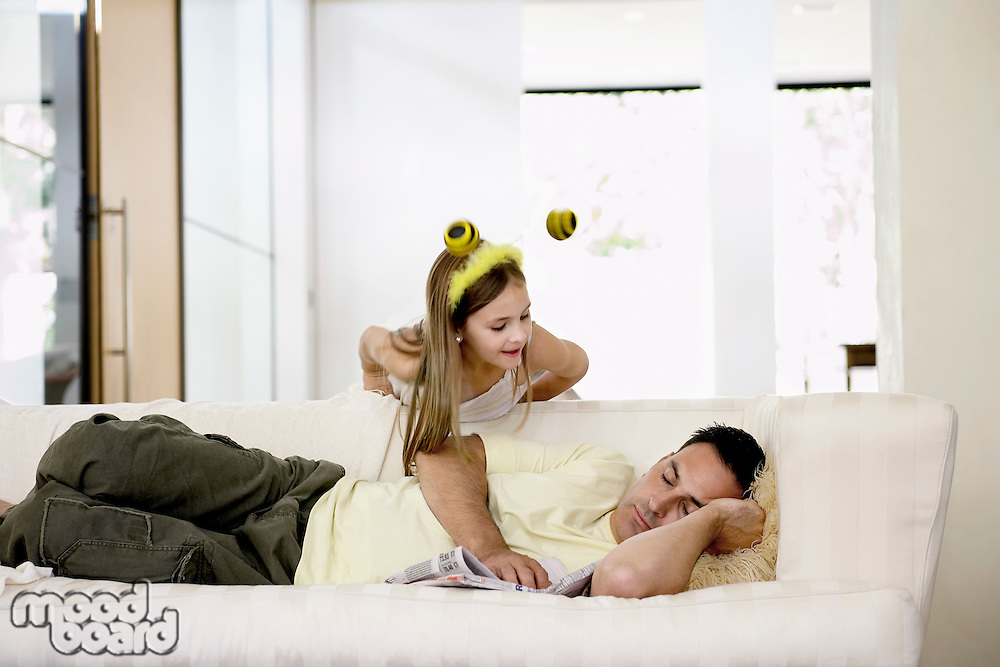 Man napping on sofa with daughter leaning over