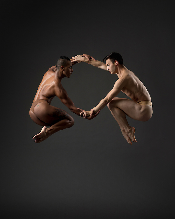 Male pax duex of contemporary dancers from Eryc Taylor dance with nude dance belts, jumping while holding hands. Taken in the photo studio on a dark grey background. Photograph taken in New York City by photographer Rachel Neville.