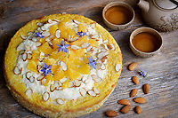 Healthy home-made flourless, sugar-free vegan fruit cake made of almond flour, oranges and coconut oil, artistic food still life on rustic wooden table background