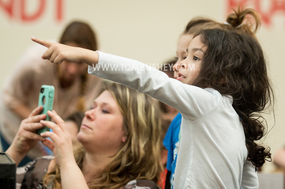 Town of Wallkill, New York - People watch a slide show presentation of art created by elementary and middle school students during the 2017 All-County Musical Showcase and Visual Arts Display at the Galleria at Crystal Run on Feb. 25, 2017.