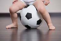 Baby boy sitting on soccer ball