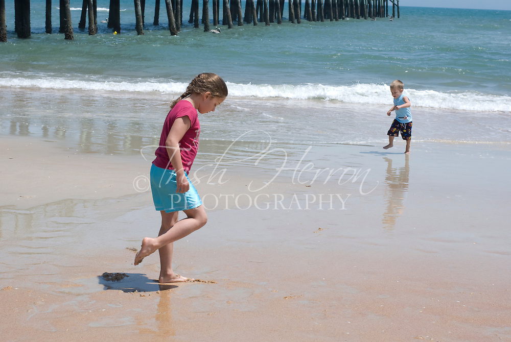 A young girl and boy play at the edge of the water at the beach on a sunny day.