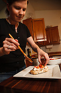 USA, Oregon, Eugene, young woman putting tomatoes on the bruschetta. MR