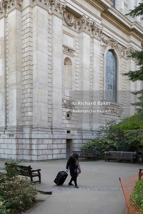 An elderly lady pulls a wheelie suitcase behind her as she walks slowly through the churchyard of St. Paul's Cathedral in the City of London, the capital's financial district, on 1st April, 2019, in London England.