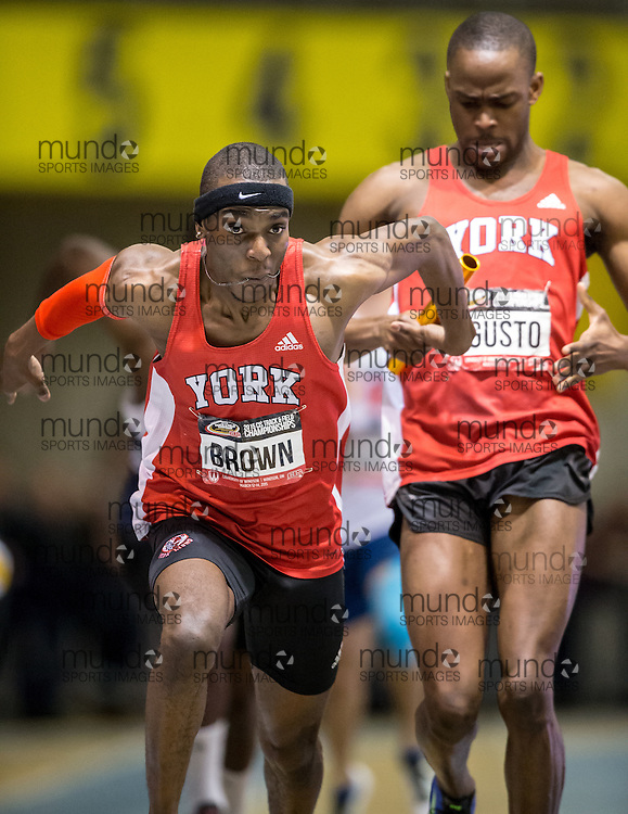 Windsor, Ontario ---2015-03-14--- Jameel Brown of York University receives the baton from teammate Ayo Agusto during their 4X200m relay final at the 2015 CIS Track and Field Championships in Windsor, Ontario, March 14, 2015.<br /> GEOFF ROBINS/ Mundo Sport Images