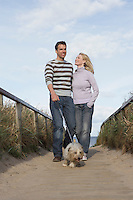 Couple walking dog on beach boardwalk