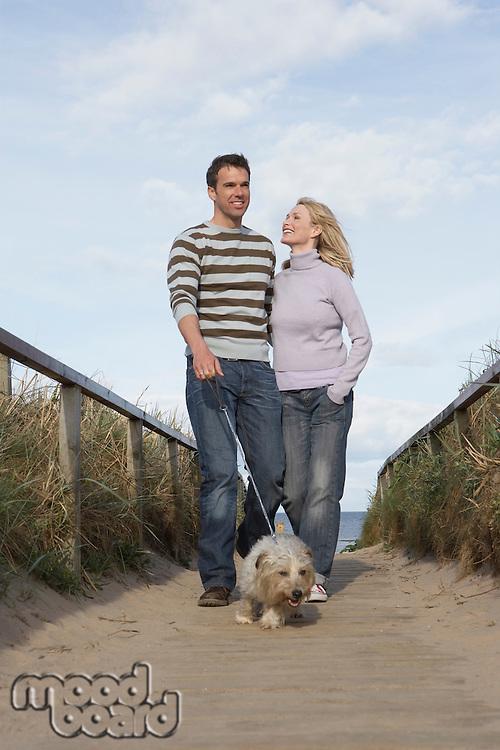 Couple walking dog on beach boardwalk