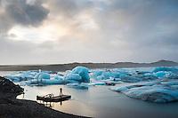 A tourist photographing by Jökulsárlón glacial lagoon, southeast Iceland. Moody sky over blue icebergs.