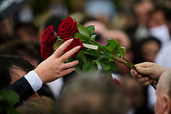 © Licensed to London News Pictures. 26/10/2017. Epsom, UK. A rose being handed over at the graveside at the funeral of Tom 'Tomboy' Doherty the nephew of Big Fat Gypsy Weddings star Paddy Doherty, at Epsom Cemetery in Epsom, Surrey. Tom Doherty was 17 when he was killed in a car crash in South Nutfield in Surrey on October 9. He had passed his driving test just days earlier. Photo credit: Ben Cawthra/LNP