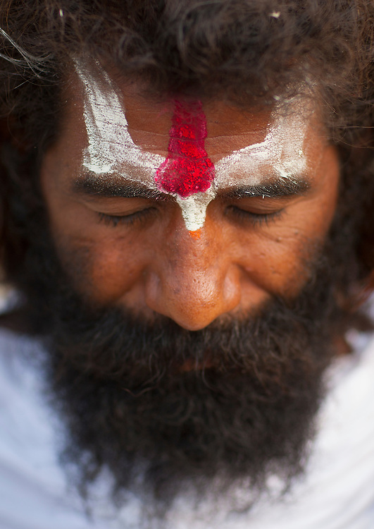 Man praying during Maha Kumbh Mela, a festival known as world's largest congregation of religious pilgrims. Allahabad, India.