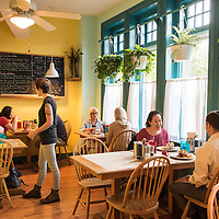 "A waitress takes orders while people dine. The Early Girl Eatery is a self-described ""farm to table southern comfort food experience."" It is located at 8 Wall Street in Downtown Asheville, North Carolina."