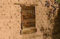 Abandoned & boarded up adobe building, window detail; Gardner, CO