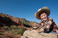 A kid having fund climbing rocks in Palo Duro Canyon