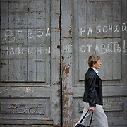 Woman walks past old wooden doors with graffiti (St Petersburg, Russian Federation - Aug. 2008) (Image ID: 080811-1548112a)