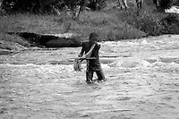 A young Congolese boy casts a net for fishing into the Epulu River, on the edge of the Okapi Wildlife Reserve, Ituri.