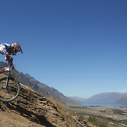 in action during the New Zealand South Island Downhill Cup Mountain Bike series held on The Remarkables face with a stunning backdrop of the Wakatipu Basin. 150 riders took part in the two day event. Queenstown, Otago, New Zealand. 9th January 2012. Photo Tim Clayton