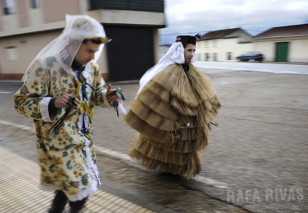 Paco Boya (R), dressed in a Tafarron costum and Jesus Ferrero (L) dressed in a Madama costum, run along streets of the north western Spanish village of Pozuelo de Tabara, Zamora province, to wake up locals, during this year's San Esteban festivities, on December 26, 2009. The pagan festival of Tafarron is one of the first winter mascarades celebrated in Zamora province. PHOTO/RAFA RIVAS
