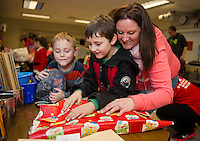 William, Cameron and Karen Lemay wrap up a present for William's big brother James during the Presents for Pleasant event on Friday evening.  (Karen Bobotas/for the Laconia Daily Sun)