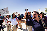 """10 MARCH 2012 - PHOENIX, AZ: LISA ESTRADA, a Veola bus driver in Phoenix, AZ, shouts at a strike breaking """"scab"""" driver during the drivers' strike Saturday. More than 600 Phoenix bus drivers, employed by Veola Transportation Services, are on strike after negotiations broke down. Drivers from Amalgamated Transit Union Local 1433 have been negotiating for more than two years with Veola. The dispute centers around wage and benefits like sick leave accrual, retirement benefits, and health care coverage. Drivers started walking their picket line early Saturday morning, March 10.      PHOTO BY JACK KURTZ"""
