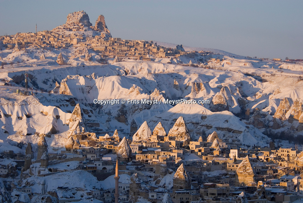 Goreme, Nevsehir, Cappadocia, Turkey. Hot air Balloons fly over the village of Goreme, with uchisar in the background. A fresh pack of snow has turned the winter landscape of Goreme National Park into an even bigger fairy tale. Photo by Frits Meyst/Adventure4ever.com
