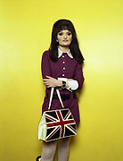 Young woman standing against a yellow background holding a handbag with union jack design.