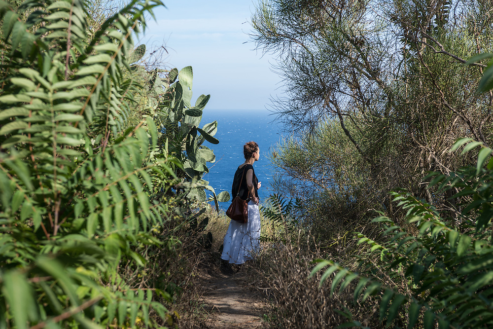 Ventotene Island, Italy - 23 September 2014: A woman looks at the view amidst the wild vegetation