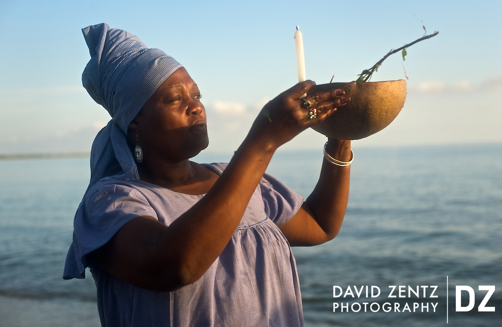 A manbo - or voodou priestess - raises a candle and calabash bowl to the four points on the compass during a sunrise voodou ritual at Bord de Mer de Limonade, on the north coast of Haiti on July 25, 2008. After renewing their faith in the mud pit at Plaine du Nord on the days prior, pilgrims migrate to the nearby water, their faith renewed.