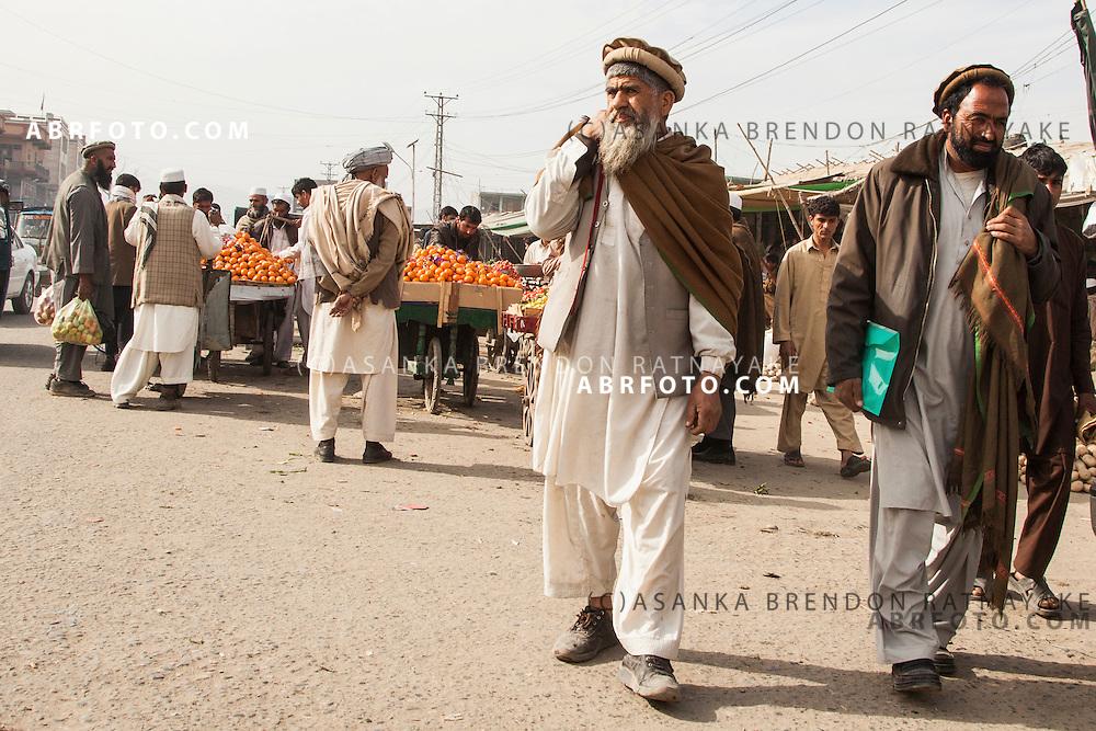 Afghan men at a street side fruit & vegtable market in Jalalabad