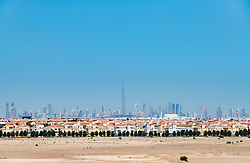 Daytime skyline of Dubai from the desert with many houses forming The Villa large luxury residential housing development in foreground in United Arab Emirates