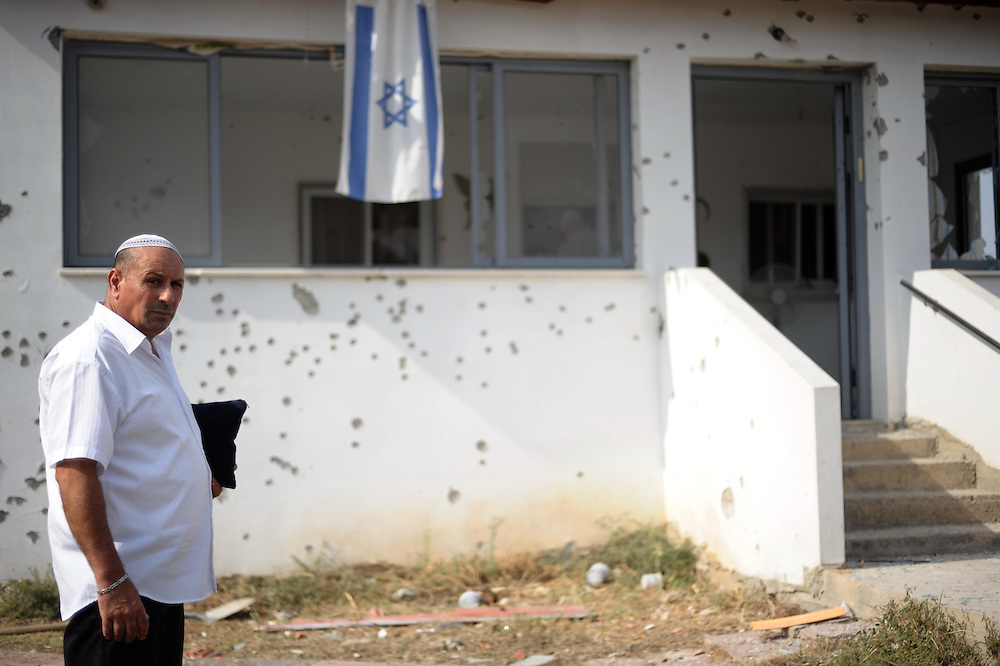 Beer Tuvia Regional Council, Israel - November 17, 2012: An Israeli man stands next to a house that was hit by a rocket fired from Gaza Strip at the fourth day of Operation Pillar of Defense. Photo by Gili Yaari  - Israel Photojournalist