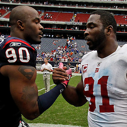 October 10, 2010; Houston, TX USA; Houston Texans defensive end Mario Williams (90) and New York Giants defensive end Justin Tuck (91) meet on the field following a game at Reliant Stadium. The Giants defeated the Texans 34-10. Mandatory Credit: Derick E. Hingle