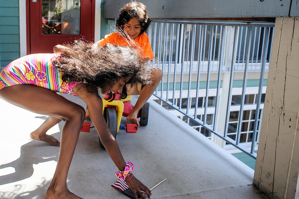 Photo by Matt Roth..Sucha Mulholland, 9, left, and Tony Wilson, right, play on the third floor walkway of the Takoma Village Cohousing complex in Washington, D.C., Saturday, September 22, 2012.