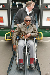 Bus driver on tailgate of specialised vehicle helping visually-impaired wheelchair user with white stick at a resource for people with physical and sensory impairment.