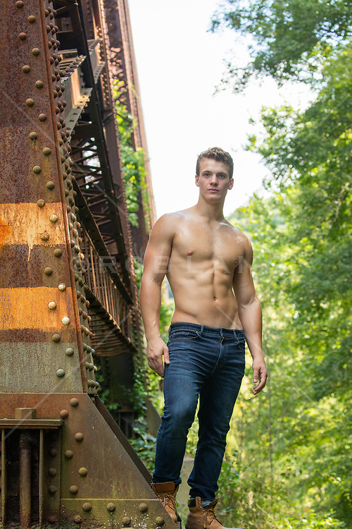 sexy man without a shirt by a railroad trestle