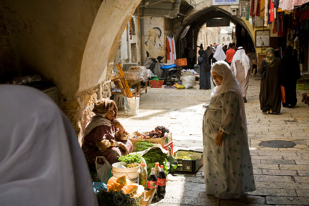 A woman speaks to a vendor selling vegetables on the street in Old City, Jerusalem, Israel.