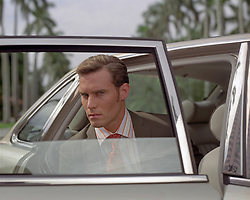 man in a suit and tie looking out a car window in Palm Beach, FL