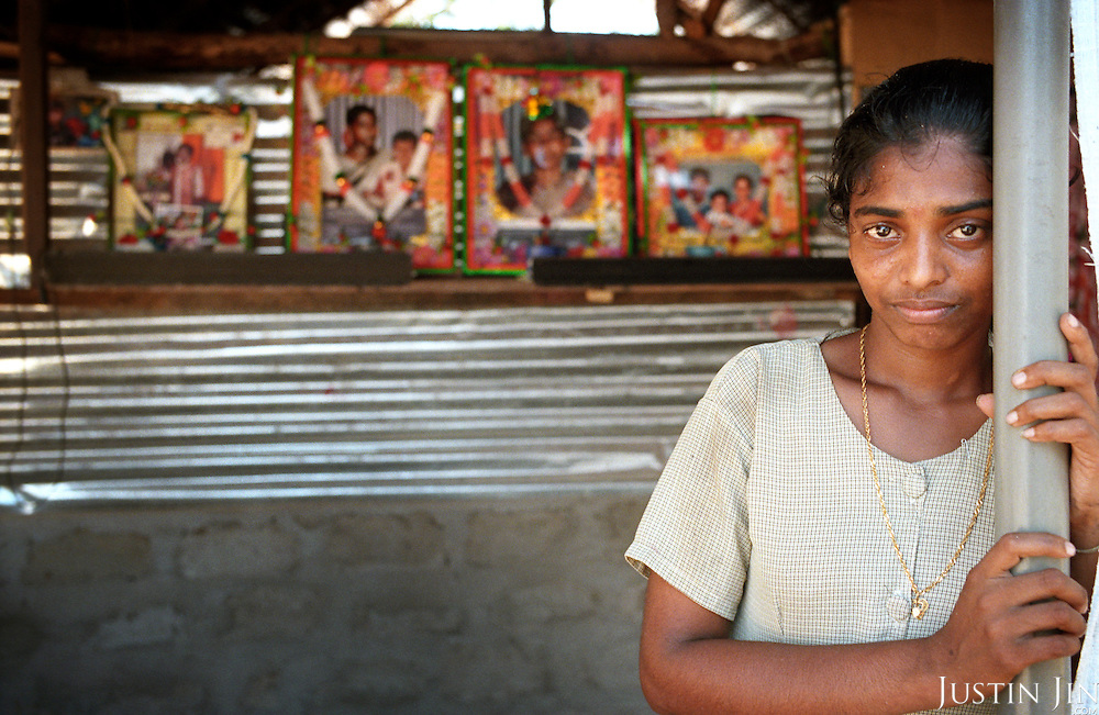V. Anitha, 22, stands in front of photos of her loved ones lost to the tsunami at her refugee hut in the northeastern coast of Sri Lanka, an area ravaged also by civil war. .Anitha lost her only child, her mother, brother and sister to the waves. .The December 26, 2004 tsunami killed around 40,000 people along Sri Lanka's southern, eastern and northern shores, tearing thousands of families apart. .The bulk of the dead were women and children - husbands lost young brides and around 4,000 children lost one or both parents. .Even before the tsunami struck, people here in the northeast had already been displaced four times by the Tigers' two-decade war for autonomy. .In some places, the scars of war and the tsunami have become one. Remnants of walls torn down by waves are pockmarked with bullet holes and shrapnel from shells fired before a 2002 ceasefire plunged a civil war that killed over 64,000 people into limbo. ..Picture taken March 2005 by Justin Jin