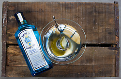 Martini made with Bombay Sapphire Gin and McClure Pickles made by James Moreland set upon  a rustic wooden apple box. Photograph by © Jackie Neale Chadwick