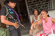 Sept. 29, 2009 -- BAAN TROKBON, THAILAND: A Thai woman Ranger talks to residents of a Buddhist village in Pattani province in Thailand. The 39 women in the 44th Army Ranger Regiment are the only Thai women seeing front line active duty against Moslem insurgents in Thailand's deep south provinces of Pattani, Narathiwat and Yala. All of the other women serving in Thai security services are employed as office and clerical workers. The Ranger women are based at the Ranger camp in the Buddhist village of Baan Trokbon in Sai Buri district of Pattani province. The unit was formed in 2006 after Muslims complained about the way Thai soldiers, all men, treated Muslim women at roadblocks and during security sweeps. The women are frequently called upon to back up Thai regular army units when they are expected to encounter a large number of Muslim women. At least two of the women have been killed by Muslim insurgents. The unit has both Muslim and Buddhist members. Many of the women in the unit joined after either their fathers or husbands were killed by insurgents.    Photo by Jack Kurtz / ZUMA Press