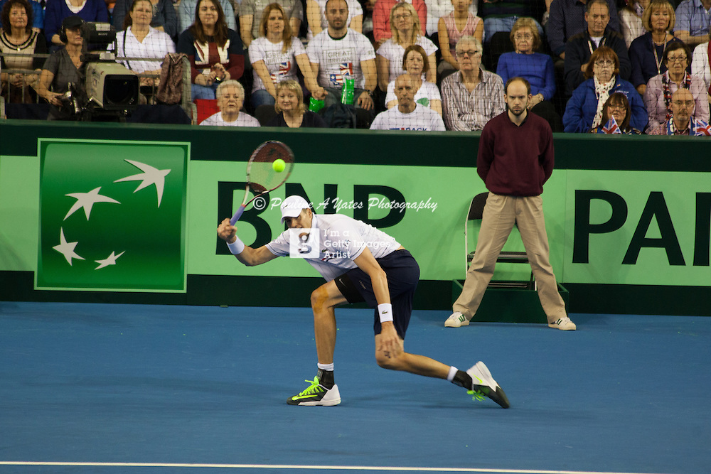 John Isner stoops to return Andy Murray's shot.