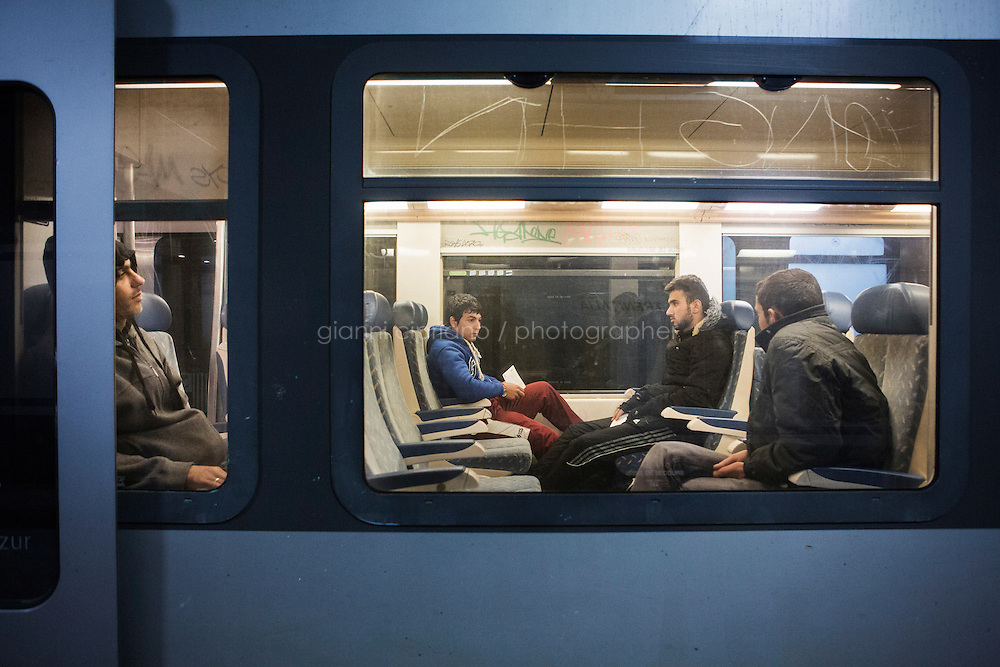 VENTIMIGLIA, ITALY - 18 NOVEMBER 2014: Syrian refugees take  the train that goes from Ventimiglia to Nice, taken by migrants that want to cross the border from Italy to Francein Ventimiglia, Italy, on November 18th 2014.<br /> <br /> The Ventimiglia-Menton border is the border between Italy and France crossed by migrants who decide to continue their journey up north towards countries such as Germany, Sweden, The Netherlands and the UK where the process to receive the refugee status or humanitarian protection is smoother and faster. in Ventimiglia, Italy, on November 17th 2014.
