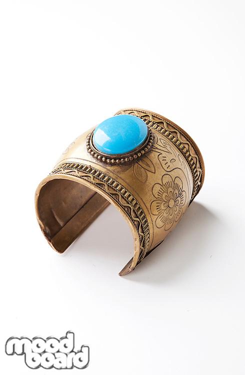 Blue gem on traditional bracelet over white background