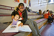 24 JANUARY 2010 -- WENDEN, AZ:  Antonia Soberanes (CQ) reads to her daughter, Brittney Soberanes (CQ) in the Red Cross shelter in Salome. They are from Wenden. Wenden was slammed by its second 100 year flood in 10 years on Thursday night when water raced through Centennial Wash and into the small town in La Paz County west of Phoenix. Most of the town's residents were evacuated to Red Cross shelters in Salome, about 5 miles west of Wenden.    PHOTO BY JACK KURTZ